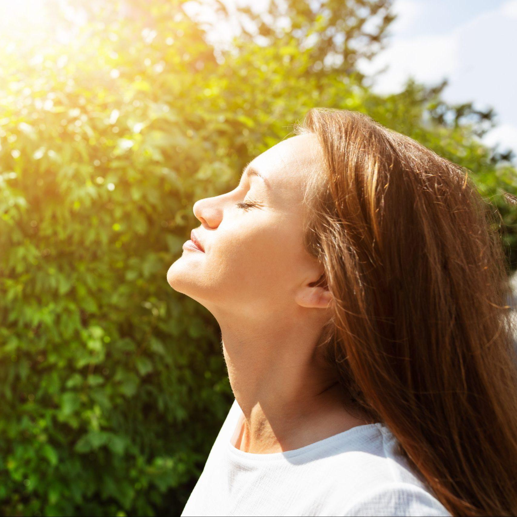 Frau steht in der Sonne vor einem Busch